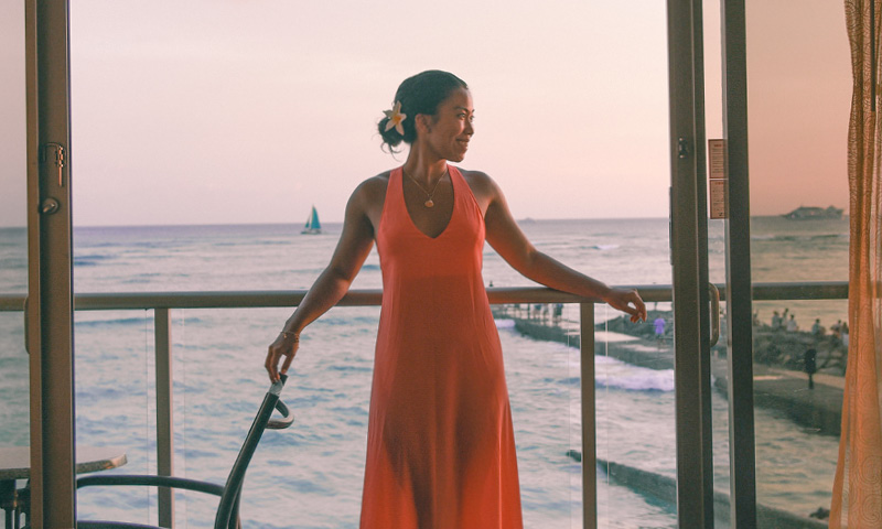 woman on balcony lanai with ocean and sunset sailboat beach background