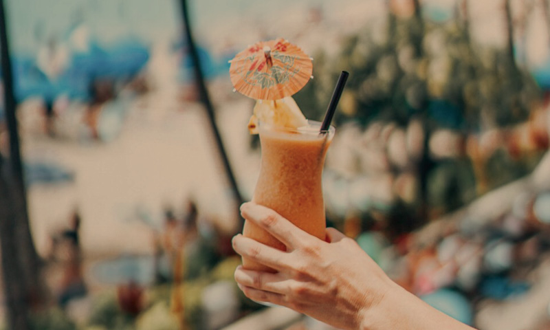 Holding Tropical Cocktail Drink on Waikiki Beach