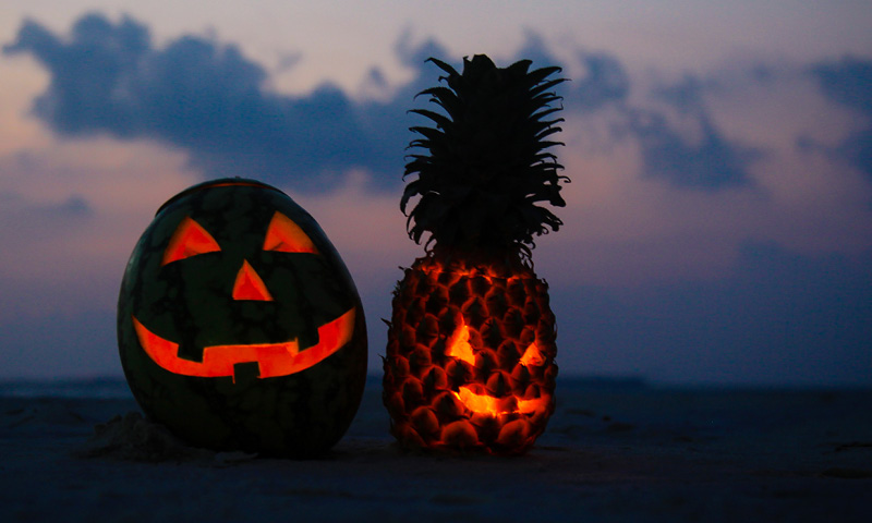 Carved Pumpkin and Pineapple Glowing on Beach