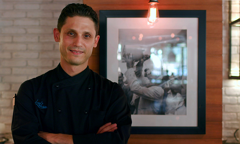 Chef Mustafa to the left of a wall portrait